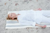 pohled na atraktivní blonďatou ženu s zavřenýma očima, když leží na rohožce jódy