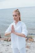 attraktive junge Frau mit geschlossenen Augen und betenden Händen am Meer