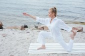 Photo attractive blonde  young woman doing yoga near sea