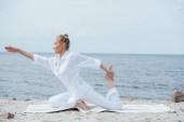 pohled na atraktivní dívku praktikující jómu u moře