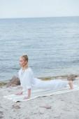 atraktivní blondýnka se zavřenýma očima, která cvičila jóga blízko řeky na rohožce jóga