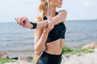cropped view of athletic girl stretching and listening music in earphones near sea
