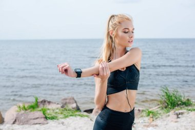 sportive girl stretching while listening music in earphones near sea