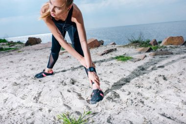 sportive woman stretching while listening music in earphones near sea
