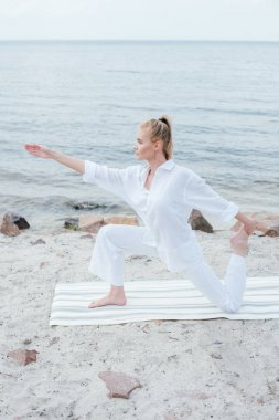 side view of attractive blonde woman practicing yoga on yoga mat near sea