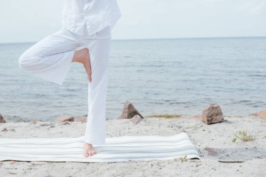 cropped view of young woman doing yoga near sea