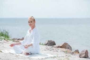 Happy blonde woman practicing yoga near sea stock vector