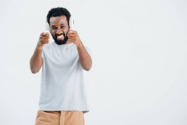 Excited african american man pointing and listening music with headphones, isolated on grey stock vector