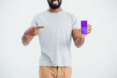 KYIV, UKRAINE - MAY 17, 2019: Cropped view of african american man pointing at smartphone with shopping app, isolated on grey stock vector