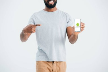 KYIV, UKRAINE - MAY 17, 2019: cropped view of african american man pointing at smartphone with android app, isolated on grey stock vector
