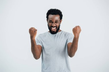 excited african american man in grey t-shirt posing isolated on grey
