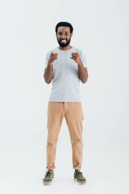 Smiling african american man in grey t-shirt pointing isolated on grey stock vector