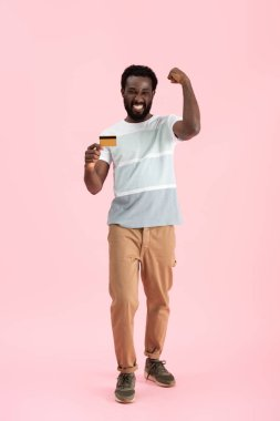 successful african american man showing credit card isolated on pink