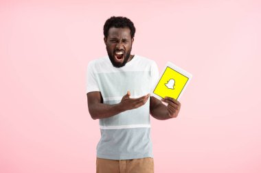KYIV, UKRAINE - MAY 17, 2019: emotional african american man shouting and showing digital tablet with Snapchat app, isolated on pink stock vector