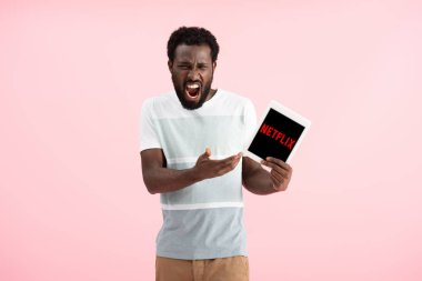 KYIV, UKRAINE - MAY 17, 2019: emotional african american man shouting and showing digital tablet with netflix app, isolated on pink stock vector