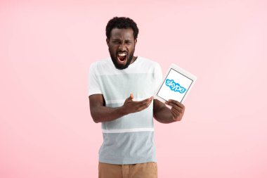 KYIV, UKRAINE - MAY 17, 2019: emotional african american man shouting and showing digital tablet with skype app, isolated on pink stock vector