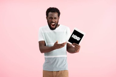 KYIV, UKRAINE - MAY 17, 2019: emotional african american man shouting and showing digital tablet with HBO app, isolated on pink stock vector