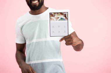 KYIV, UKRAINE - MAY 17, 2019: cropped view of african american man showing digital tablet with foursquare app, isolated on pink stock vector