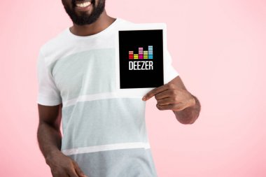 KYIV, UKRAINE - MAY 17, 2019: cropped view of african american man showing digital tablet with deezer app, isolated on pink stock vector