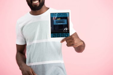 Cropped view of smiling african american man showing digital tablet with booking app, isolated on pink stock vector
