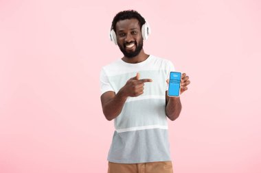 KYIV, UKRAINE - MAY 17, 2019: african american man listening music with headphones and pointing at smartphone with skype app, isolated on pink