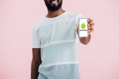 KYIV, UKRAINE - MAY 17, 2019: cropped view of african american man showing smartphone with android app, isolated on pink stock vector