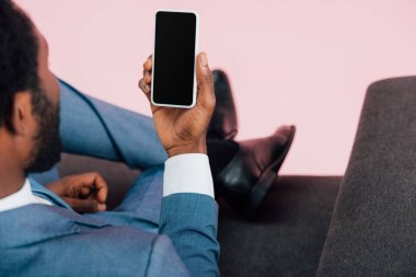 Cropped view of african american businessman sitting in armchair and holding smartphone with blank screen, isolated on pink stock vector