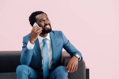 Handsome african american businessman sitting in armchair and talking on smartphone, isolated on pink stock vector