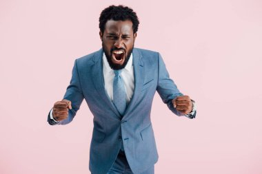 aggressive african american businessman in suit shouting isolated on pink