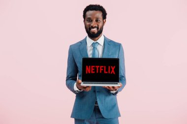 KYIV, UKRAINE - MAY 17, 2019: smiling african american businessman showing laptop with netflix website, isolated on pink stock vector