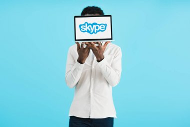 KYIV, UKRAINE - MAY 17, 2019: african american man showing laptop with skype, isolated on blue stock vector