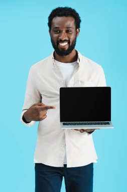 Smiling african american man pointing at laptop with blank screen isolated on blue stock vector