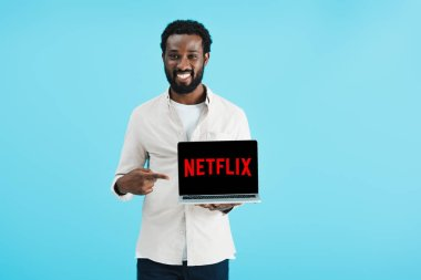 KYIV, UKRAINE - MAY 17, 2019: smiling african american man pointing at laptop with netflix website, isolated on blue stock vector