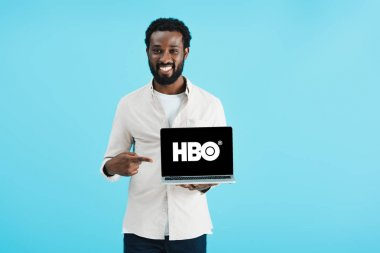 KYIV, UKRAINE - MAY 17, 2019: smiling african american man pointing at laptop with HBO website, isolated on blue stock vector