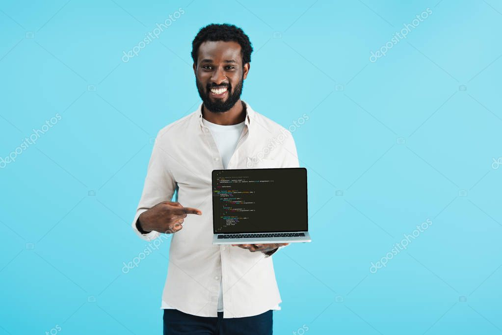 KYIV, UKRAINE - MAY 17, 2019: smiling african american man pointing at laptop with html code, isolated on blue