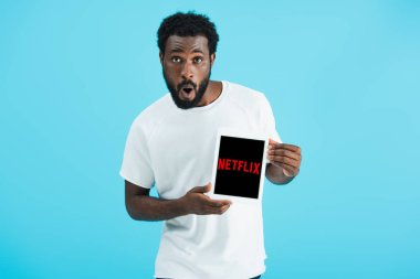 KYIV, UKRAINE - MAY 17, 2019: surprised african american man showing digital tablet with netflix app, isolated on blue stock vector