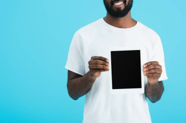 Cropped view of african american man in white t-shirt showing digital tablet with blank screen isolated on blue stock vector