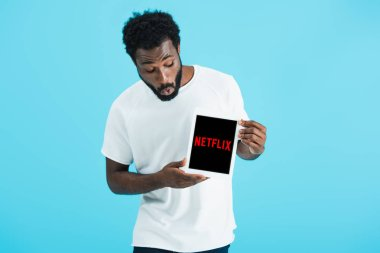 KYIV, UKRAINE - MAY 17, 2019: shocked african american man looking at digital tablet with netflix app, isolated on blue stock vector