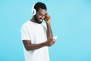 Cheerful african american man listening music with headphones and using smartphone, isolated on blue stock vector