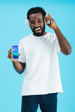 Smiling african american man listening music with headphones and showing smartphone with booking app, isolated on blue stock vector