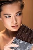 krásná mladá nahá žena držící čokoládovou tyčinčku ve stříbrné fólii a ohlížel izolovaně na béžový