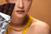 Fotografie částečný pohled na nahou mladou ženu se žlutou měřicí páskou držící čokoládovou tyčinku izolovanou na béžové
