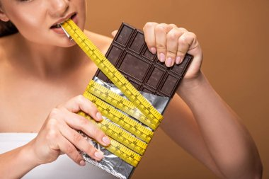 partial view of young woman holding yellow measuring tape in mouth and chocolate bar isolated on beige