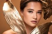 krásná mladá nahá žena s ozdobnými zlatými listy izolovanými na béžové