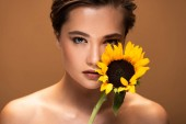beautiful young nude woman holding yellow sunflower isolated on brown