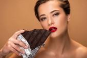 schöne nackte Frau mit roten Lippen halten Schokoriegel in Silberfolie isoliert auf Beige