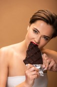 beautiful woman with red lips biting chocolate bar in foil isolated on beige
