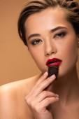Fotografie attraktive junge Frau hält Schokoladenstück in der Nähe des Mundes isoliert auf beige