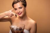 Fotografie glücklich schöne Frau zeigt Finger in geschmolzener Schokolade isoliert auf beige