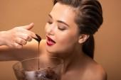 nackte Frau mit roten Lippen isst geschmolzene Schokolade aus Schüssel isoliert auf beige